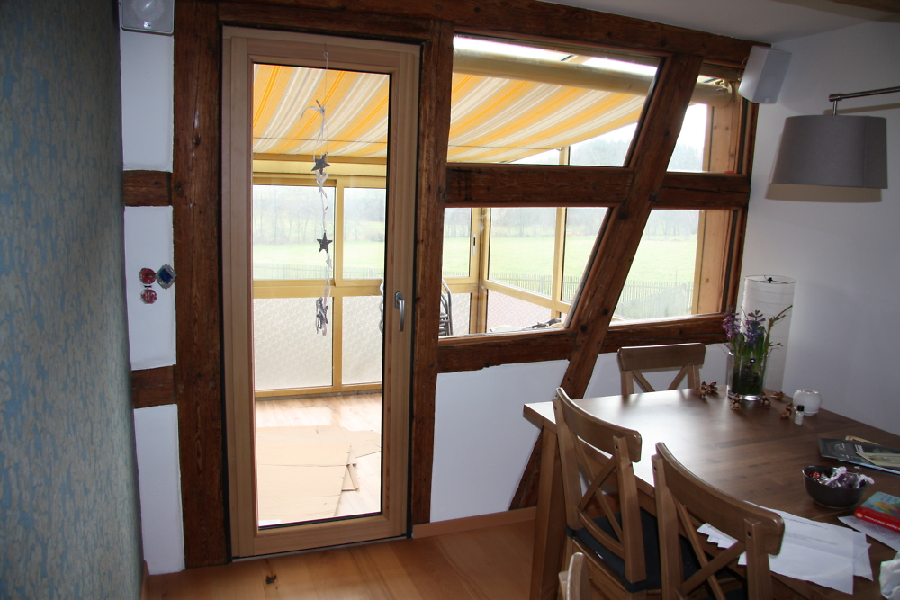 Balcony door with cladding of the framework
